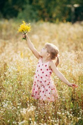 Sweet little girl in a meadow with wild spring flowers