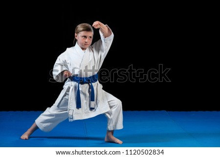 sweet little girl in martial arts practice like karate kid alone isolated on black background