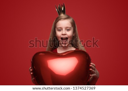 Sweet little girl in princess crown holding heart shaped balloon and screaming in amazement while celebrating Valentines Day against red background