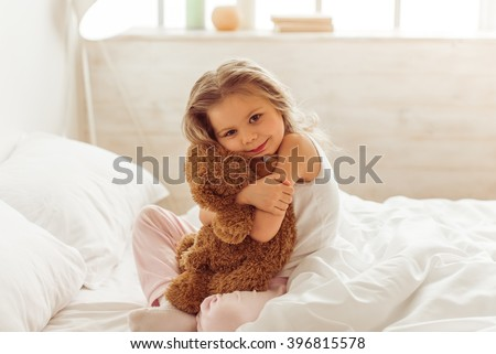 Stock Photo Sweet little girl is hugging a teddy bear, looking at camera and smiling while sitting on her bed at home