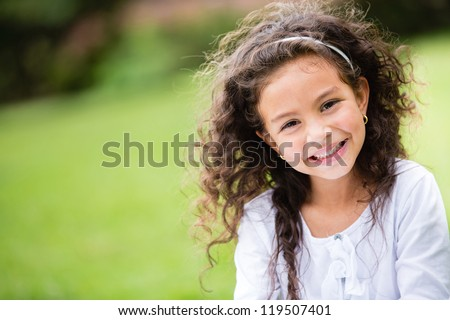 Sweet little girl outdoors with curly hair in the wind #119507401