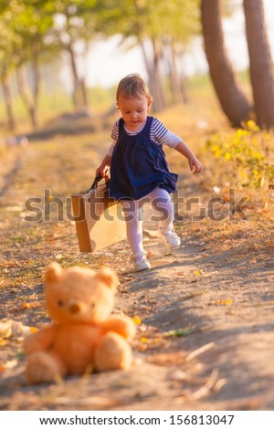 Sweet little girl playing with suitcase and teddy bear on the country road