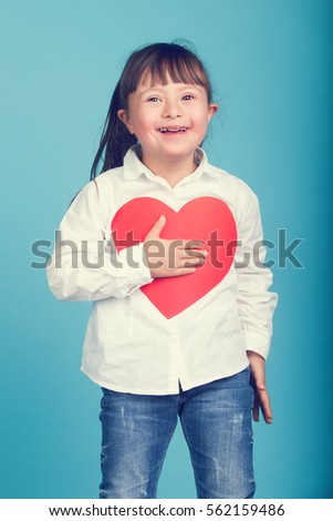 Sweet little girl with Down Syndrome, playing with paper heart #562159486