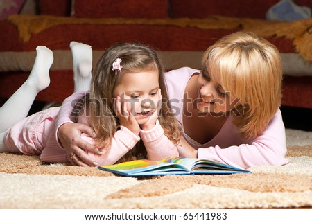 sweet  little girl with mother reading book