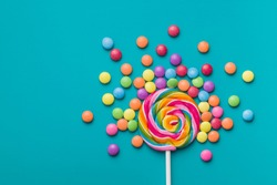 Sweet lollipop and colorful chocolate candy pills on blue background.