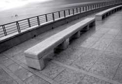 Sweet melancholy in the autumnal light of the sea of Grado on the stone benches in Nazario Sauro seafront