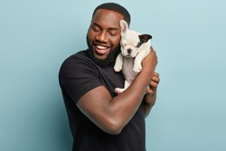 Sweet moments with domestic animals. Portrait of satisfied dark skinned man holds cute small french dog puppy closely to face, enjoys good time with loyal pet, wears casual black t shirt, pose indoor
