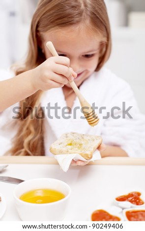 Sweet morning - little girl preparing to eat honey on bread, focus on the hand