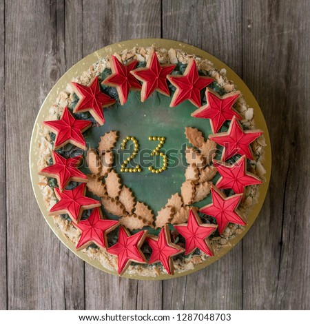 Sweet Napoleon cake with decor on 23 february holiday - Red stars cookies and number 23 - on wooden background. Close up, Selective focus #1287048703