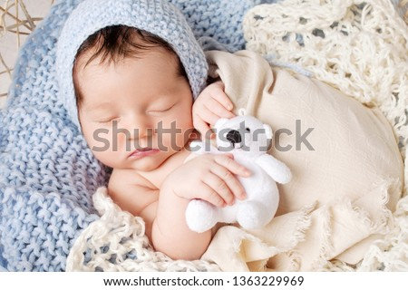 Sweet newborn baby sleeps in a basket. Beautiful newborn boy with bear toy.