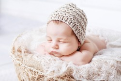 Sweet newborn baby sleeps with a toy in the basket. Newborn boy folded handles  in a basket. Close up image. White background.