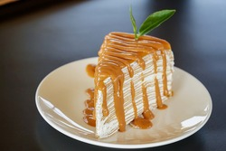 Sweet or dessert, a Thai milk tea Crepe Cake topping with Thai milk tea sauce and decor with tea leaf on white plate on black table with a cafe environment