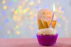 Sweet organic happy birthday cupcake with burning candle in purple wrap, cream cheese frosting swirl and golden chocolate decoration on white wooden textured table. Close up, copy space, background.