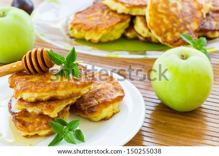 sweet pancakes with apples and honey on a plate