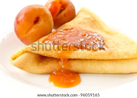sweet pancakes with apricot jam on a white plate