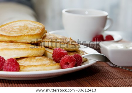Sweet pancakes with raspberries, sour cream and  cup of tea