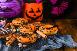 Sweet pastries decorated for a horror party. Halloween donuts on a wooden background. Copy space. Top view. High quality photo