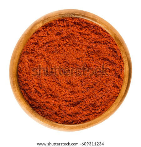 Shutterstock Sweet pepper red paprika powder in wooden bowl. Ground spice made from air-dried and smoked bell peppers, Capsicum annuum. Hungarian cuisine. Macro food photo close up from above on white background.