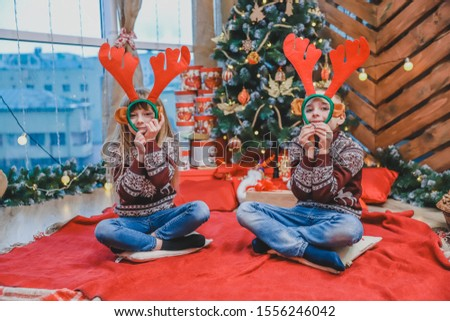 Sweet photo of cheerful sister and brother playing around putting reindeer headgear in front of their faces.