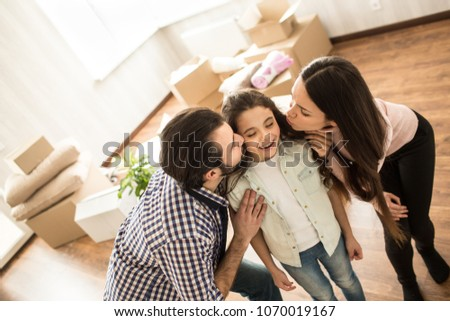 Sweet picture of happy family. Man and woman are kissing their daughter in cheeks. Small girl looks happy and adorable.