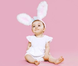 Sweet pink cute baby sitting in costume easter bunny with fluffy ears