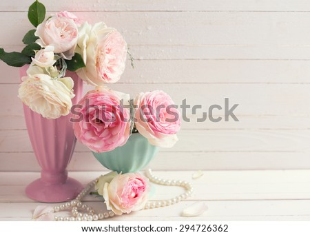 Sweet pink roses flowers in vases on white painted wooden background against white  wall. Selective focus. Place for text. Toned image.