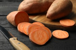 Sweet potato, board and knife on wooden background, close up