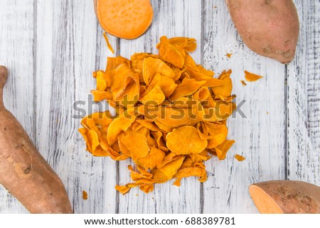Sweet Potato Chips as high detailed close-up shot on a vintage wooden table; selective focus
