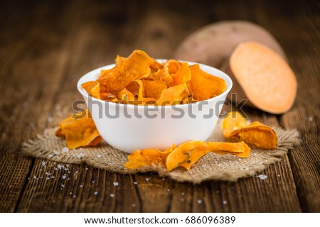 Sweet Potato Chips on an old wooden table as detailed close-up shot; selective focus