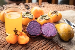 sweet potato, persimmon and orange juice on wooden background