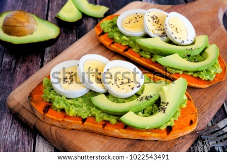 Sweet potato toasts with avocado, eggs and chia seeds on a wood board. Table scene with a wooden background. #1022543491