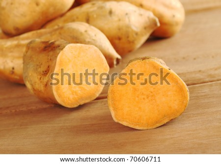 Sweet potatoes halves (lat. Ipomoea batatas) on wooden surface (Selective Focus, Focus on the half in the front)