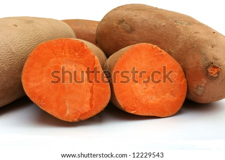 Sweet Potatoes, two halves of a cut sweet potato in front of whole sweet potatoes