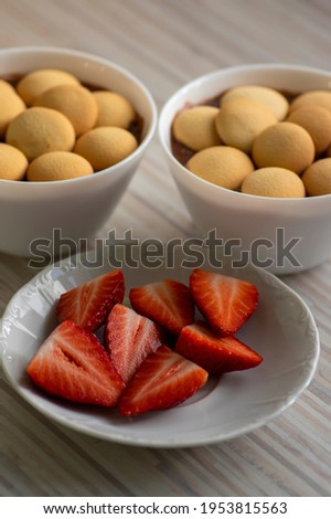 Sweet poudding with small sponge cakes in bols and fresh raw red ripened strawberries, group of fruits cut in halves served on white plate on wooden table Photo stock ©