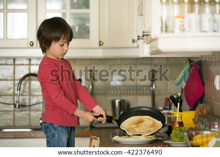 Sweet preschool child, helping his mom in the kitchen, making pancakes in the morning, happy childhood