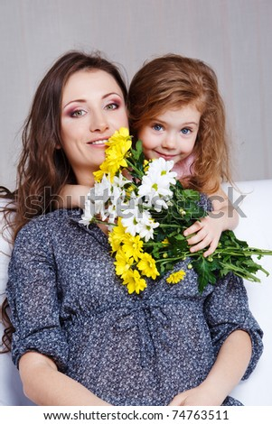 Sweet preschool girl embracing mom and presenting her flowers bunch