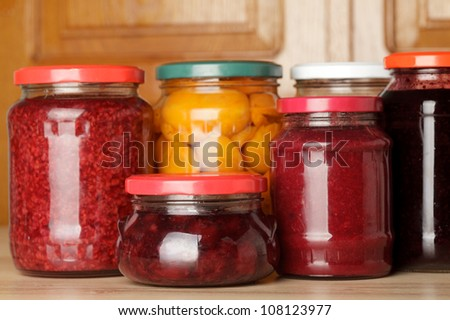 Sweet preserves as jams and compotes on table in kitchen