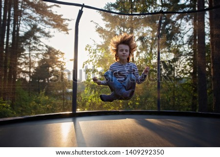 Sweet preteen boy jumping on trampoline making somersaults in the air. Child levitating. Happy child jumping on sunset #1409292350