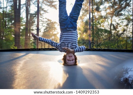 Sweet preteen boy jumping on trampoline making somersaults in the air. Child levitating. Happy child jumping on sunset #1409292353
