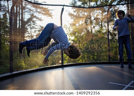 Sweet preteen boy jumping on trampoline making somersaults in the air. Child levitating. Happy child jumping on sunset #1409292356