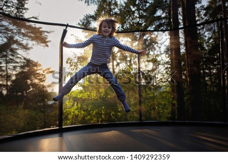 Sweet preteen boy jumping on trampoline making somersaults in the air. Child levitating. Happy child jumping on sunset #1409292359