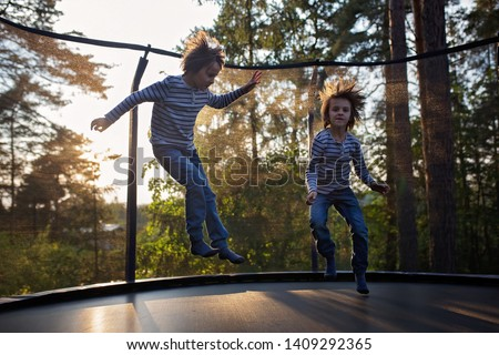 Sweet preteen boy jumping on trampoline making somersaults in the air. Child levitating. Happy child jumping on sunset #1409292365