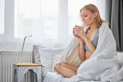 sweet pretty caucasian woman in underwear drink hot coffee or tea on bed at home. good-looking lady after waking up