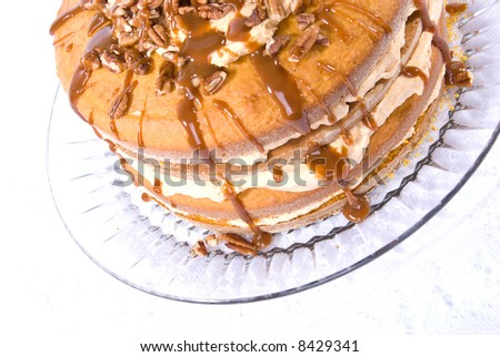 sweet pumpkin cake dessert with cream filling and pecans on top drizzled with caramel topping on clear plate - stock photo