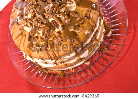 sweet pumpkin cake dessert with cream filling and pecans on top drizzled with caramel topping on clear plate