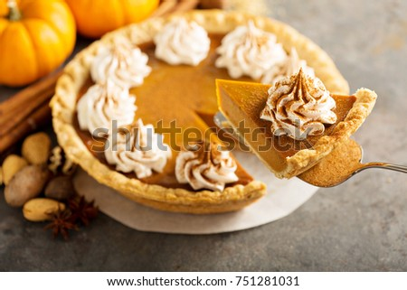 Sweet pumpkin pie decorated with whipped cream and cinnamon with a slice taken out #751281031