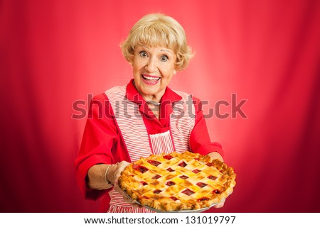 Sweet retro grandmother holding a freshly baked lattice top cherry pie.  Red background with plenty of room for text.