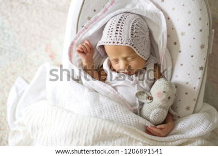 sweet sleeping newborn in a retro cap with a handmade toy, light style and an innocent tender childhood, sound sleep #1206891541