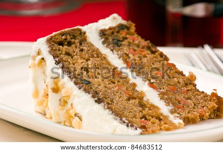Sweet slice of walnut carrot cake on white plate. Shallow depth of field.