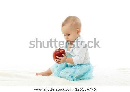 Sweet small baby with a fresh red apple on a white background
